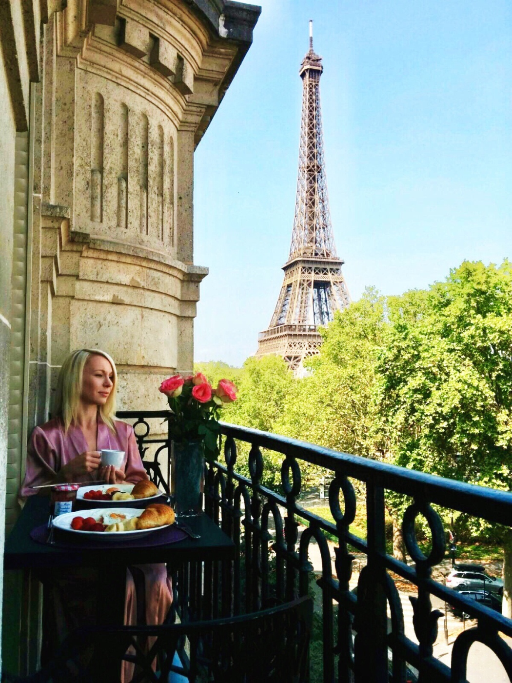 Blonde girl sits on a balcony and eats breakfast with the view of the Eiffel Tower in the background in Paris France