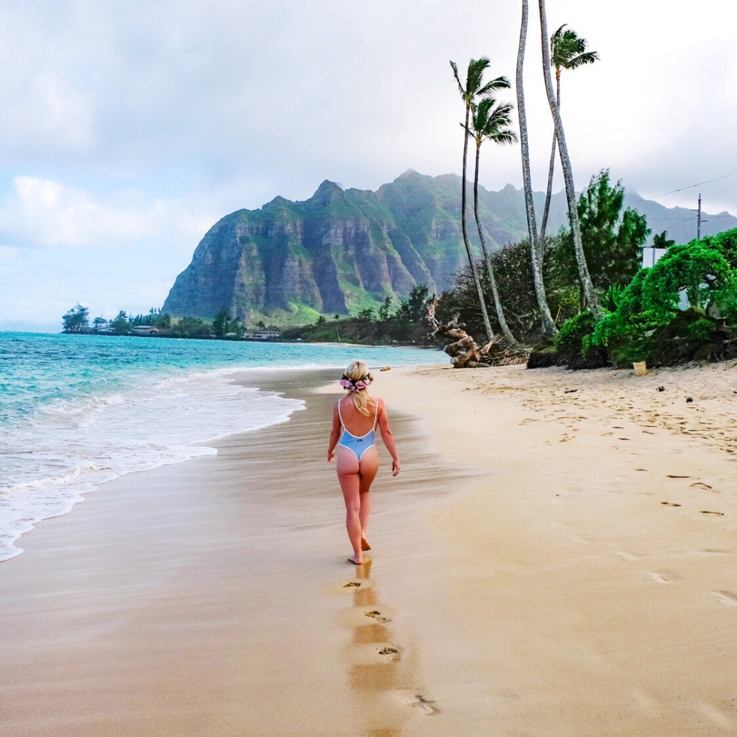 Blonde girls walks down famous Kaaawa beach in a Boutinela bikini on Oahu, Hawaii